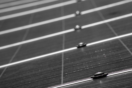 conductive: A low angle view in black and white of a solar pannel as it stretches away from the camera in to the distance.