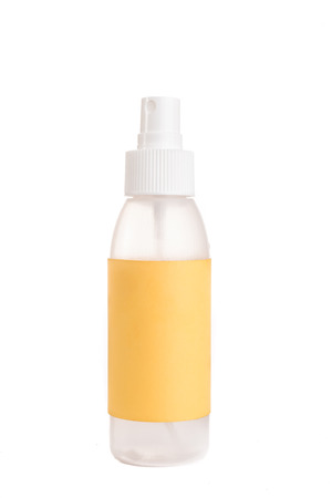 containment: A plastic spray bottle with a yellow label and a white top on a white background. Stock Photo