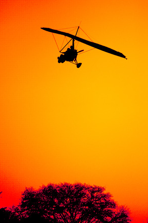 high view: The silhouette of an ultra light aircraft on final approach as it comes in for landing against the red orange sky of a beautiful sunset at Victoria Falls in Zambia.