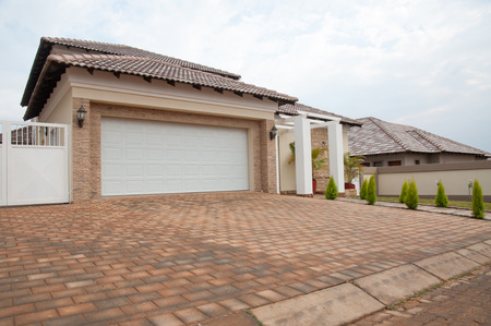 A Newly build suburban house viewed from the front to reveal the paving of brick and the white double garage door next to the entrance of the house. Banco de Imagens