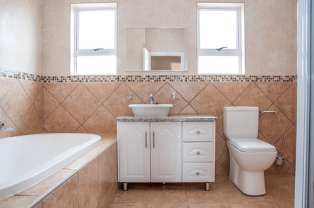 corner tub: The brand new bathroom of a newly build house, revealing the bath, basin, and the toilet, all in white, in front of brown tiles on the wall. Stock Photo