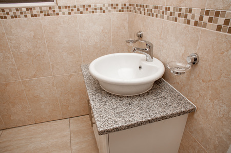 tiled wall: A white round basin positioned on a white granite topped build in cupboard inside a bathroom that is tiled with light brown ceramic tiles from top to bottom in a brand new home.