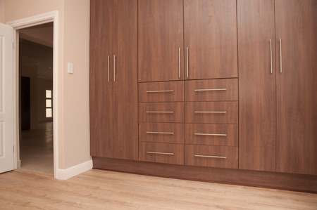 build in: View of dark brown build in wooden cupboards of an empty bedroom in a newly build house. Next to the cupboards is the entrance to the bedroom and the floor is of laminated wood.