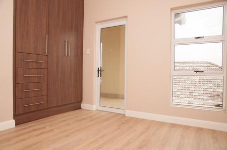 cupboards: An empty bedroom of a new home with dark brown wooden cupboards, light brown laminated floor, aliminium frame winows and glass door to the patio, as viewed from inside the room.
