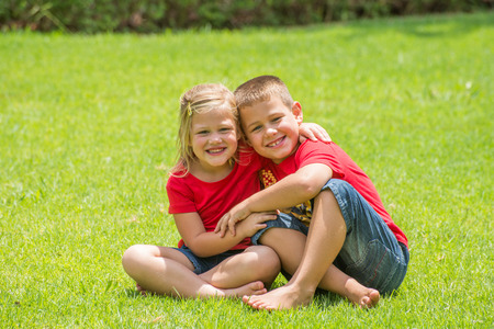 sit around: Two children who are brother and sister sit by each other with arms around the neck on the lawn as the smile and pose for a photograph.