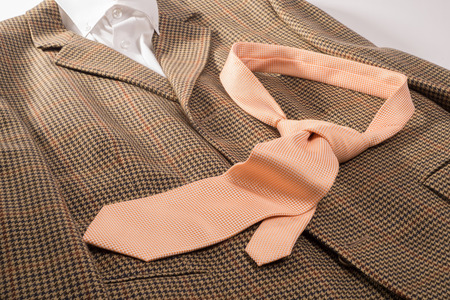 An orange and white dotted tie , already in a knot, lies on a brown sports jacket together with a white color shirt. Stock Photo
