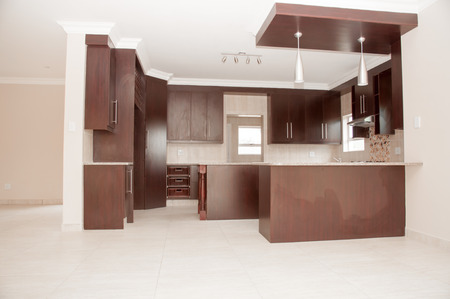 tiled stove: A brand new designer kitchen of dark brown wood in a new house with a tiled floor and white ceiling.