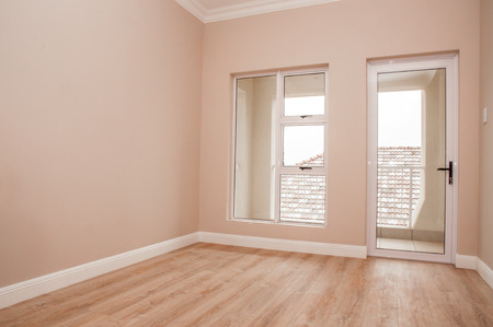 build: An Empty bedroom of a newly build house with laminated floor and glass windows and door that lead out to the patio.