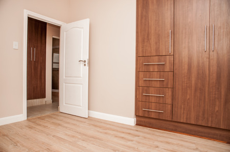 skirting: Bedroom of New House with build in cupboards, and laminated floor, as viewed towards the open door to the bedroom. Stock Photo