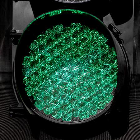 trafic stop: LED powered traffic light, shining green, viewed up close. Stock Photo