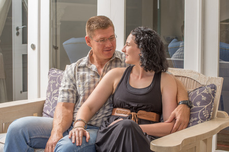 A young couple sit together on the porch of their home. Stock Photo