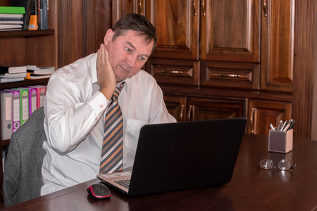 midlife: A man in his midlife sits in his stydy in front of a laptop while rubbing his neck as he stresfully looks at the screen.