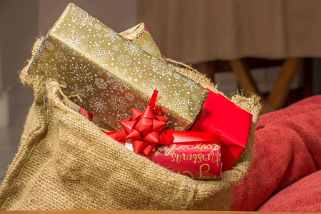 hessian bag: Christmas presents stacked to the brim inside a brown hessian bag resting near some red pillows inside a home.