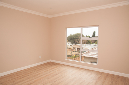 dwelling: The interior of an empty bedroom, looking towards the window over the laminated floor, of a newly build house.