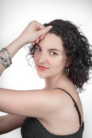 twentysomething: Portrait of a young woman with black hair and a black open shoulder top sitting sideways in front of a white background while looking towards the camera.