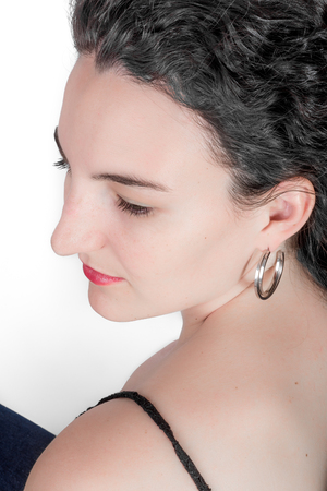 mid twenties: Young model in her mid twenties with black hair on a white background as viewed from the side. Stock Photo