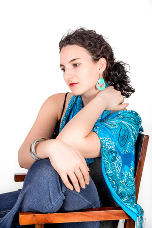 mid twenties: Young model in her mid twenties wearing aqua colored earrings of middle eastern design and a blue shawl.