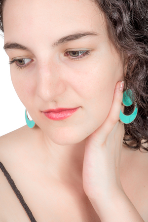 twentysomething: Young female model with open shoulder dress and aqua colored earrings of middel eastern design.