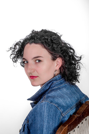 mid twenties: Young model in her mid twenties sitting on a wooden chair with a blue denim jacket.