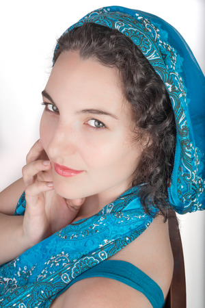 twentysomething: Young female model with black hair and a blue open shoulder summer dress, wearing a blue shawl over her hair.