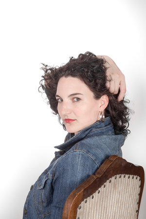 mid twenties: Portrait of a Young model in her mid twenties sitting on a wooden chair with a blue denim jacket, head turned to camera, and hand in hair, all in front of a white background.