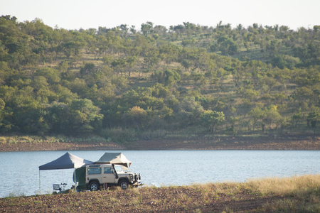 breakaway: A four by four vehicle by the water with tents and fishing rods set up.