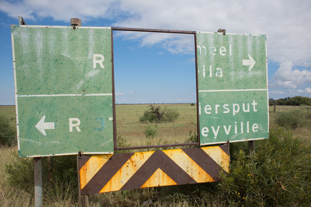 An old deteriorated road sign next to the road with a big rectangular piece in the middle completely missing serve as a frame for the landscape in the background Stock Photo