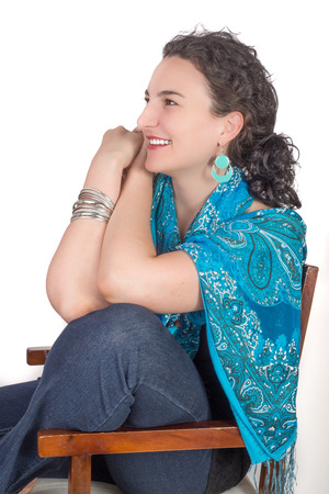 mid twenties: Young model in her mid twenties wearing aqua colored earrings of middle eastern design and a blue shawl sits on a wooden chair and smiles while looking in to the distance.