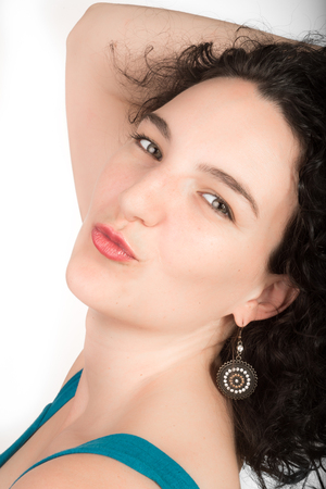 twentysomething: Young female model with black hair, blue open shoulder dress on a white background blows kiss towards viewer with her hand in her hair.
