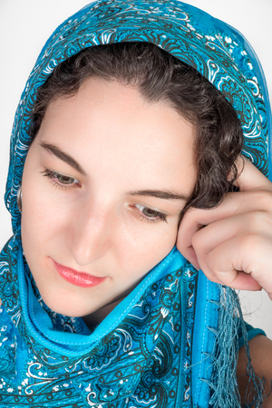 twentysomething: Young female model with black hair wearing a blue shawl over her hair held by left hand as shel looks down wards while thinking.