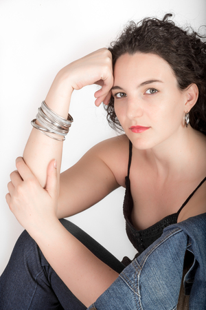 mid twenties: Young model in her mid twenties sitting on a chair with a blue denim jacket hanging over the back of the chair, head resting against hand, on white background. Stock Photo