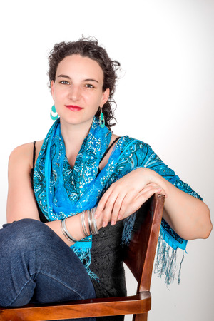 twentysomething: Young model in her mid twenties wearing aqua colored earrings of middle eastern design and a blue shawl.