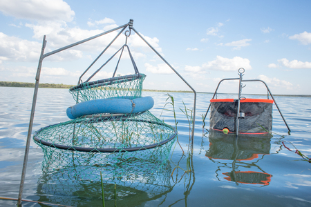 passtime: Two fishing pens are secured to the ground under the water of a dam among the vegetation with the water of the dam and white clouds among blue sky in the background. Stock Photo