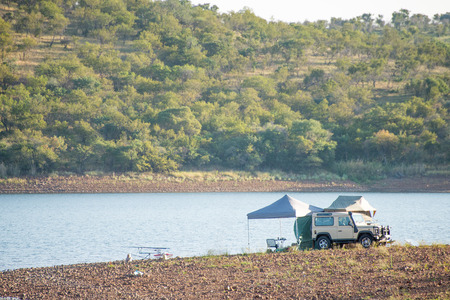passtime: A four by four vehicle by the water with tents and fishing rods set up.