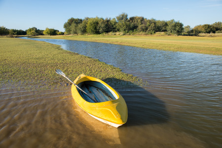 bank activities: A yellow kayak lies on the bank by the water on an early summer morning.