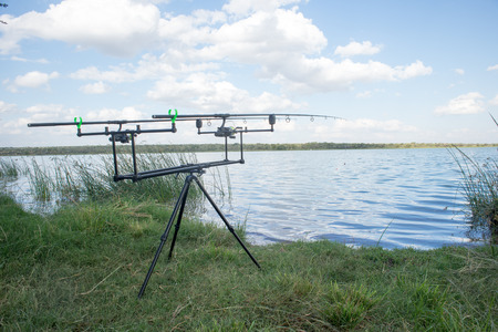 cast in place: A double fishing rod stand with cast rods in place stand in the green grass alongside the calm waters of the dam, Stock Photo