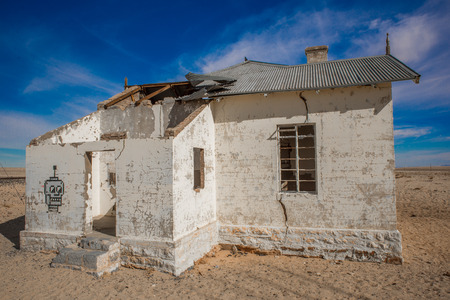 pealing: An abandoned house in the desert with white pealing paint, broken roof and graviti on the wall.
