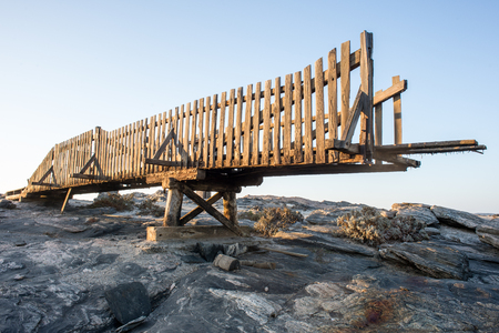 precarious: A broken wooden bridge stand neglected on the rocks by Dias Point near Ludritz in Namibia. Stock Photo