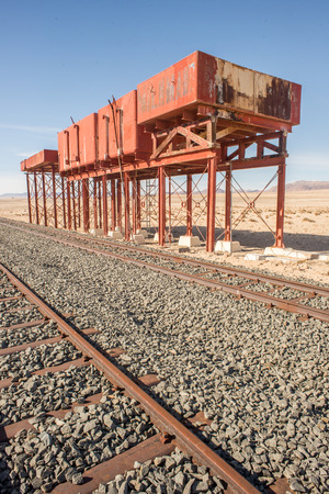 refilling: Old unused watertanks for refilling locomotives stand next to a railroad track Stock Photo