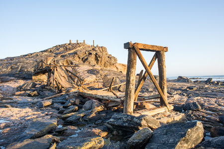 broken hill: An old wooden bridge ly in pieces on the rocks towards Dias Cross on the hill by Dias Point near Luderitz, Namibia.