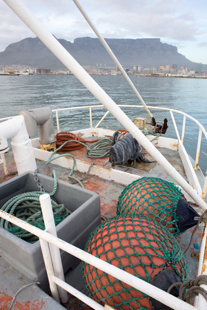 Fenders lie in the foreground as a fishing trawler enters Table Bay on its way to Cape Town.