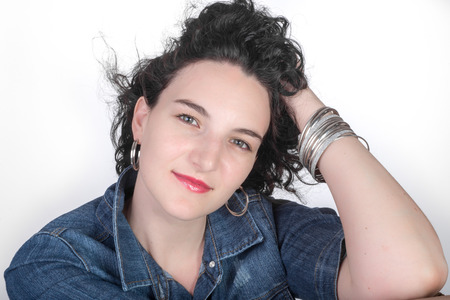 twentysomething: Young model in her mid twenties sitting in front of white background  with a blue denim jacket, and her hand in her hair.