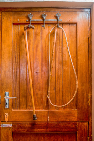 stow: A wip and a walking stick hang on hooks behind a closed wooden door. Stock Photo