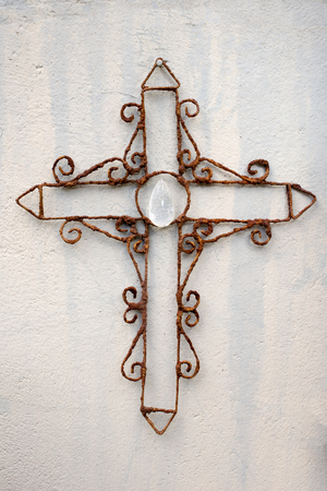 rusty wire: Front view of a rusty wire cross ornament placed against a wall. Stock Photo