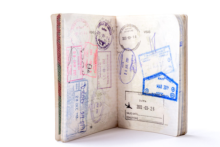 admittance: An open passport filled with stamps stand open on a white background.