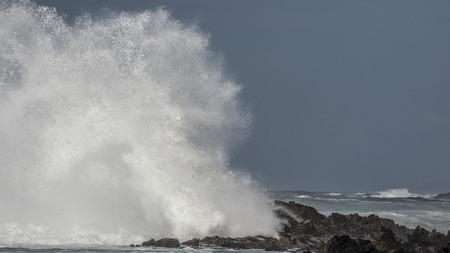 A massive wave crashes against the rocks at the shoreline at Storms River Mouth and creates a big splash.