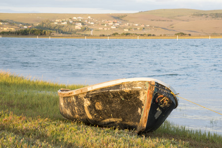 An old neglected boat lies tied with a roap on the bank of the river. Stock Photo