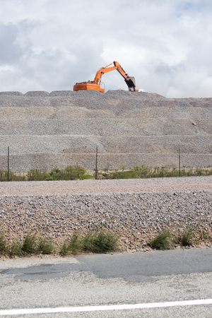 A big digging machine loads gravel in to a truck at road works. Stock Photo