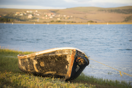 The hull of an old boat lies on the bank of the river.