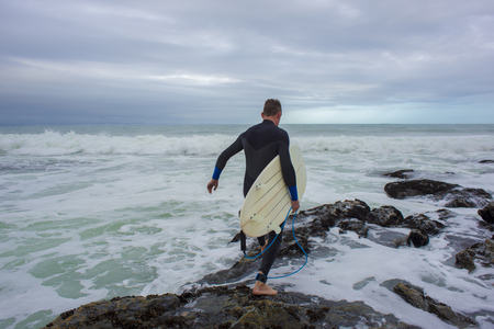 A surfer is viewed from behind as he crosses the rocks to get to the waves for a surf.